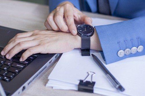 darbuotojas tikrina laikrodį